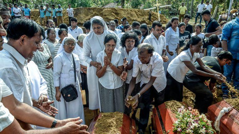 Des familles de morts offrent leurs prières lors des funérailles au village de Katuwapity