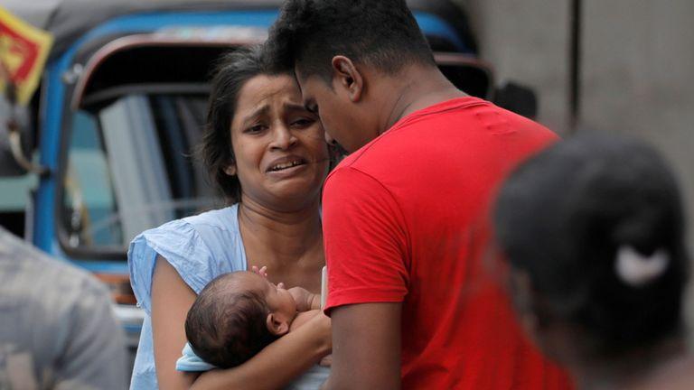 Une femme et son nouveau-né, qui habitent près de l'église attaquée hier, quittent leur domicile alors que l'armée tente de désamorcer une fourgonnette présumée avant son explosion, à Colombo, au Sri Lanka, le 22 avril 2019. REUTERS / Dinuka Liyanawatte