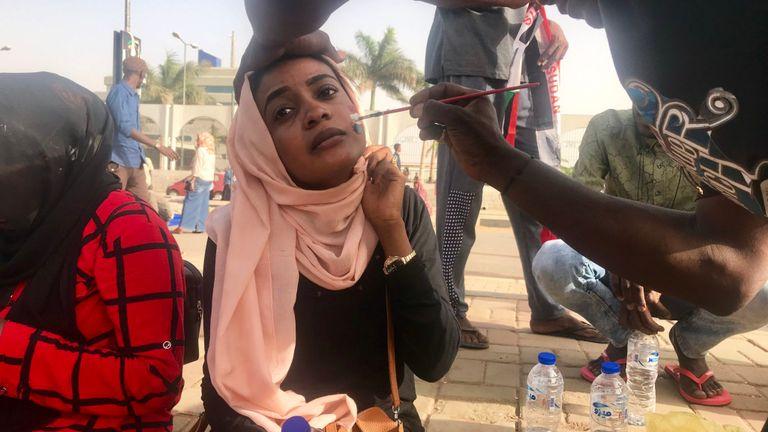 Une femme a le drapeau soudanais peint sur son visage
