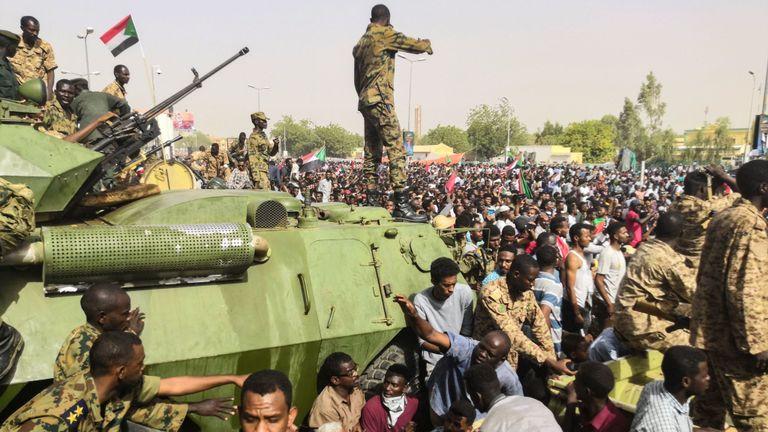 Des soldats soudanais montent la garde sur des véhicules militaires blindés dans la capitale, Khartoum