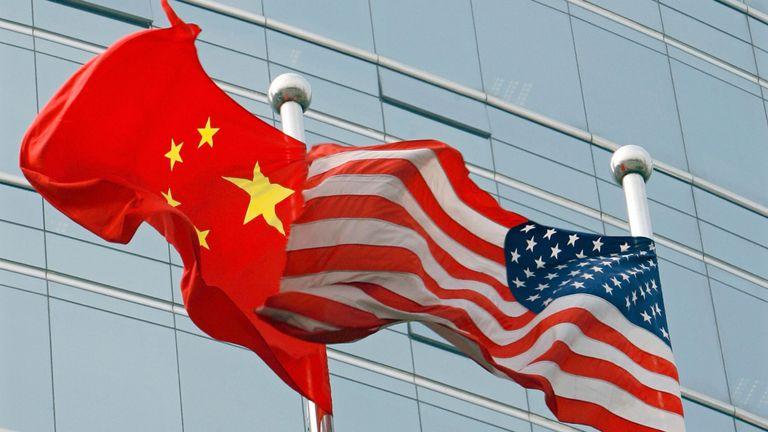 Beijing, CHINE: Les États-Unis et un drapeau chinois agitent une bannière devant un bâtiment commercial à Beijing, le 9 juillet 2007. La secrétaire d'État américaine Condoleezza Rice, le 6 juillet 2007, a accusé la Chine d'avoir fait fi des règles du commerce mondial dans son expansion économique fulgurante sous le gouvernement américain.
