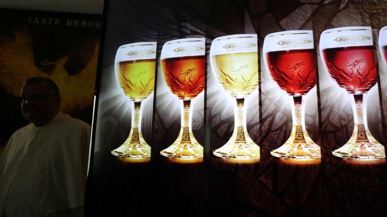 Le père Karel de Norbertine est vu derrière un tableau montrant les bières Grimbergen, symbolisées par un phénix, à l'abbaye belge de Grimbergen après avoir annoncé que les moines retourneraient à la brasserie après une pause de deux siècles, à Grimbergen, Belgique, le 21 mai 2019. REUTERS / Yves Herman