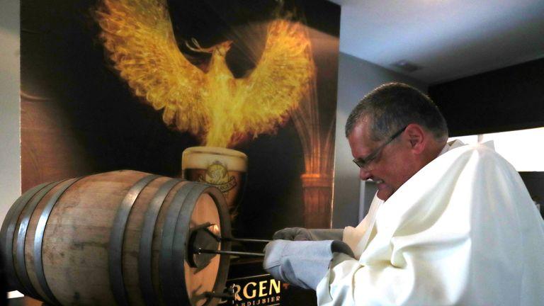 Le père Karel de Norbertine marque un tonneau de bière Grimbergen, symbolisé par un phénix, à l'abbaye belge de Grimbergen après avoir annoncé que les moines retourneraient à la brasserie après une pause de deux siècles, à Grimbergen, Belgique, le 21 mai 2019. REUTERS / Yves Herman