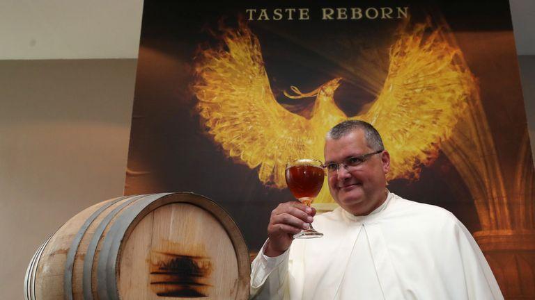 Le Père Karel Norbertine porte une bière Grimbergen symbolisée par un phénix à l'abbaye belge de Grimbergen après avoir annoncé que les moines retourneraient à la brasserie après une pause de deux siècles à Grimbergen, Belgique, le 21 mai 2019. REUTERS / Yves Herman