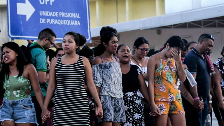 Les membres de la famille des détenus sont photographiés en train de prier devant les locaux de la prison de Puraquequara