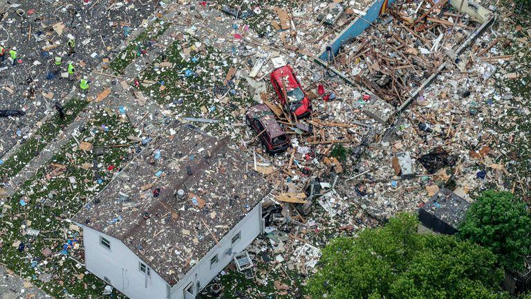 Véhicules endommagés à côté des débris de l'explosion d'une maison