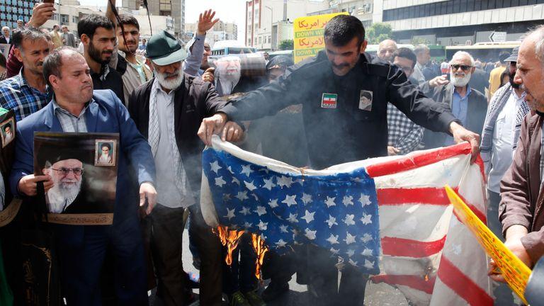 Des manifestants iraniens brûlent un drapeau américain improvisé lors d'un rassemblement dans la capitale, Téhéran