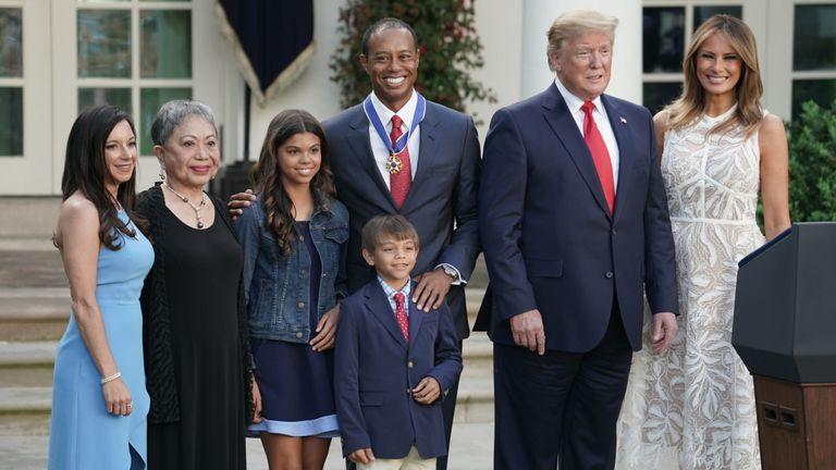 Donald et Melania Trump (à droite) posent avec Tiger Woods (au centre) et sa famille lors de la cérémonie au jardin des roses