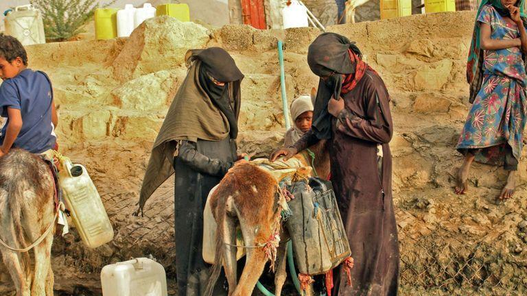Des Yéménites déplacés d'Hodeida remplissent des bidons d'eau dans un camp de fortune