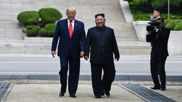 La dirigeante nord-coréenne Kim Jong Un se promène avec le président américain Donald Trump au nord de la ligne de démarcation militaire qui sépare la Corée du Nord et la Corée du Sud, dans la zone de sécurité commune de Panmunjom dans la zone démilitarisée (DMZ) le 30 juin 2019. (Photo de Brendan Smialowski / AFP) (Le crédit photo doit se lire comme suit: BRENDAN SMIALOWSKI / AFP / Getty Images)