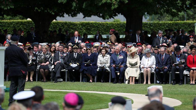 Le prince Charles et la duchesse de Cornouailles écoutent le vétéran Frank Baugh au cimetière de Bayeux