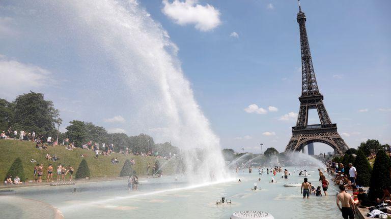 Les gens se calment dans les fontaines du Trocadéro en face de la Tour Eiffel à Paris alors qu'une vague de chaleur frappe une grande partie du pays