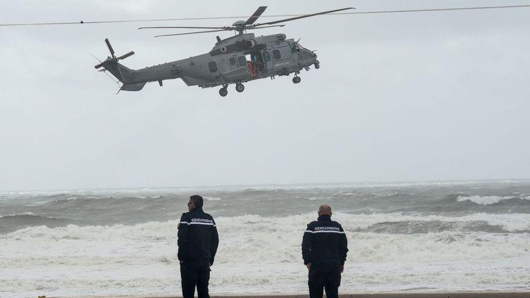 Deux gendarmes observent un hélicoptère de l'armée de l'air française survolant une plage aux Sables-d'Olonne