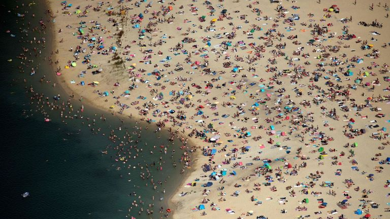 Les gens se rafraîchissent au bord d'un lac à Haltern am See, dans l'ouest de l'Allemagne, alors que les températures dépassaient les 38 ° C