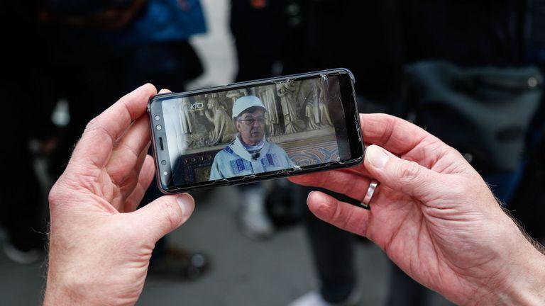 Une personne, munie d'un téléphone portable, regarde en direct l'émission de la première messe présidée par l'archevêque de Paris, Michel Aupetit, coiffée d'un casque de protection dans une chapelle latérale de la cathédrale Notre-Dame de Paris à la suite de l'incendie dévastateur du 15 avril, à Paris, le 15 juin 2019. - La cathédrale Notre-Dame de Paris accueillera sa première messe le 15 juin 2019, exactement deux mois après l'incendie dévastateur qui a secoué la France et le monde. Pour des raisons de sécurité, la messe présidée par l'archevêque de Paris Michel Aupetit