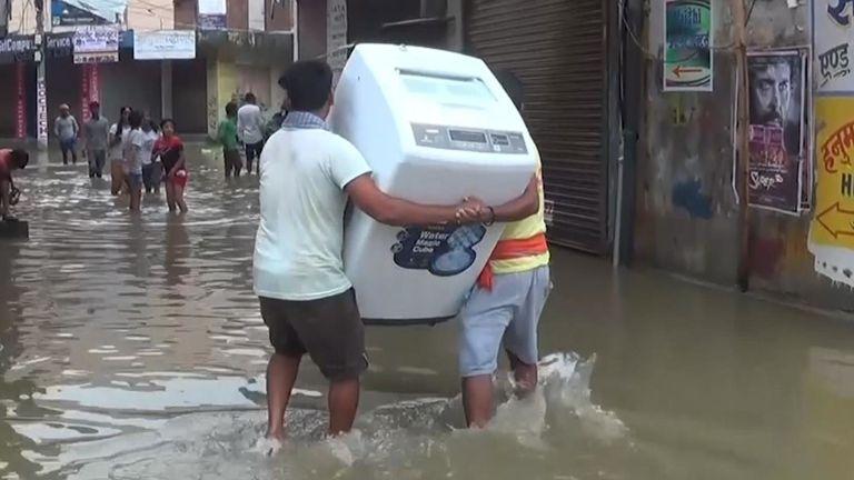 Les hommes portent un réfrigérateur loin des eaux de crue