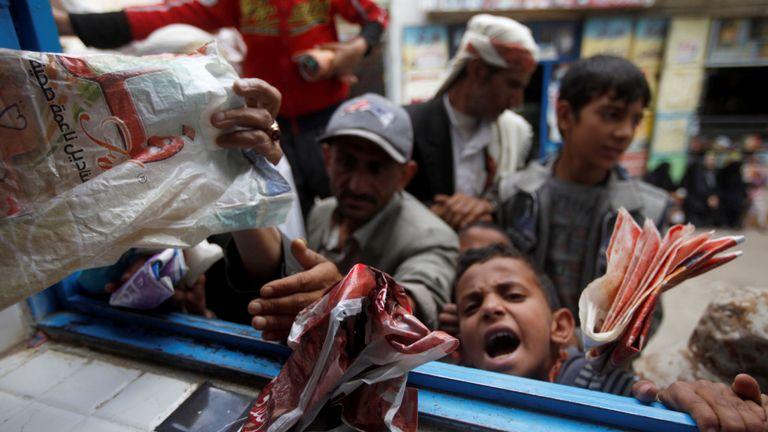 Des garçons font la queue pour obtenir du pain dans une boulangerie de charité à Sanaa, capitale du Yémen