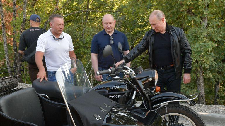 Le président russe Vladimir Poutine se tient à côté d'une moto de l'Oural lors d'un salon organisé par un club de motards