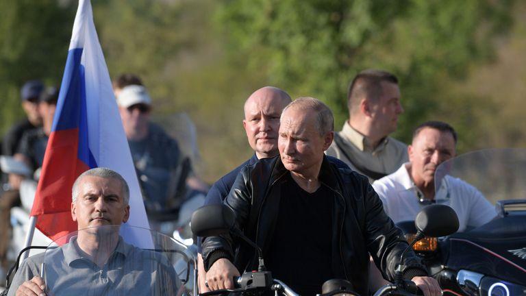 Le président russe Vladimir Poutine, le gouverneur par intérim de Sébastopol Mikhaïl Razvozhayev et le chef de la Crimée Sergueï Aksyonov conduisent une moto de l'Oural pour participer à un spectacle organisé par un club de motards