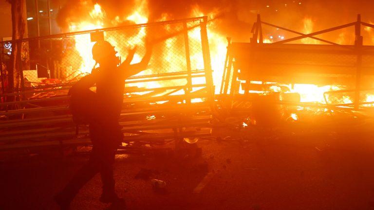 Un manifestant se tient à côté d'une barricade en feu