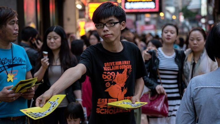 Le 16 novembre 2014, Joshua Wong (C), dirigeant étudiant de Hong Kong, distribue des tracts en soutien aux manifestations pour la démocratie en faveur de la démocratie dans la région de Causeway Bay à Hong Kong