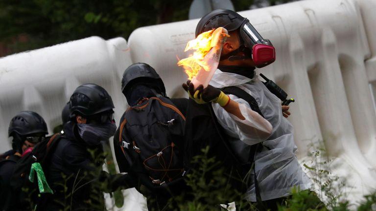 Des manifestants jettent des cocktails Molotov sur un bâtiment gouvernemental lors d'une manifestation à Hong Kong, Chine samedi