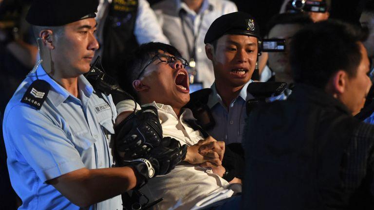 Joshua Wong (C), militant pour la cause de la démocratie, hurle alors qu'il est emmené par la police après que lui-même et d'autres manifestants ont organisé un sit-in pour protester contre la statue de Golden Bauhinia, remise à Hong Kong par la Chine pour marquer le transfert en 1997, devant la Centre de congrès et d'expositions à Hong Kong le 28 juin 2017