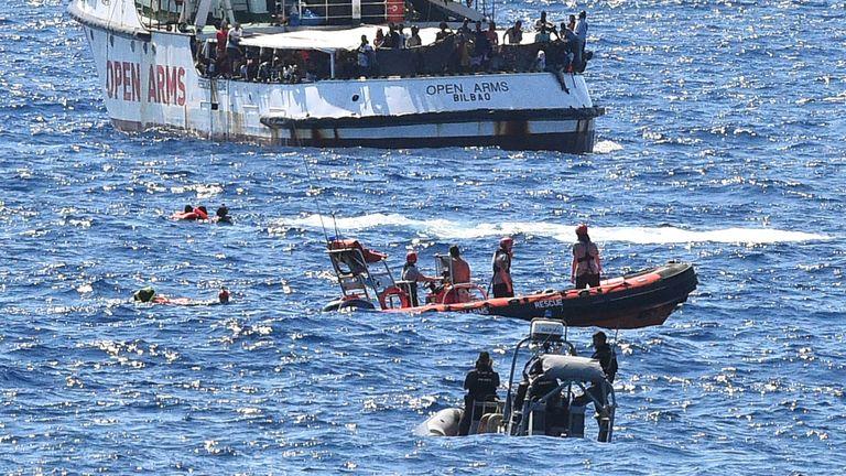 Des migrants nagent après avoir sauté du navire de sauvetage espagnol Open Arms, près de la côte italienne à Lampedusa, en Italie