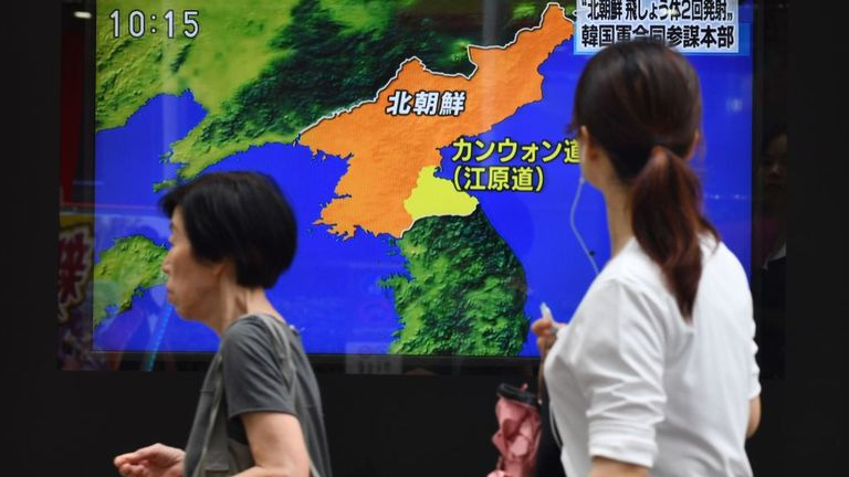Au Japon, des piétons passent devant un écran de télévision au bord de la route pour rendre compte du lancement de projectiles par la Corée du Nord.
