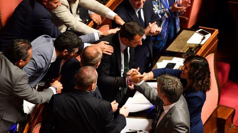 Des membres du parti d'extrême droite de la Ligue félicitent le Vice-Premier ministre et ministre de l'Intérieur Matteo Salvini (C) à la suite de son discours devant le Sénat italien à Rome le 20 août 2019