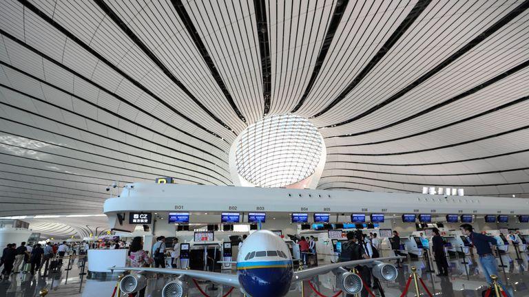 Des personnes marchent à l'intérieur du nouvel aéroport international de Beijing Daxing lors de sa première journée d'opération à Beijing, le 25 septembre 2019. - Le nouvel aéroport futuriste de Beijing, qui devrait devenir l'un des plus achalandés au monde, a été ouvert par le président chinois Xi Jinping le 25 septembre. (Photo de STR / AFP) / China OUT (le crédit photo devrait correspondre à STR / AFP / Getty Images)