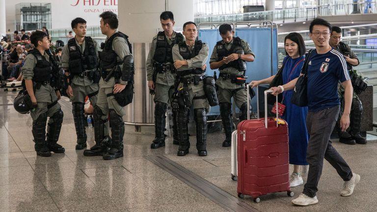 Les passagers passent devant la police surveillant l'entrée de l'aéroport international de Hong Kong