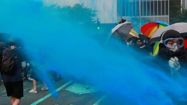 Une eau de couleur bleue est pulvérisée sur les manifestants anti-gouvernementaux lors d'une manifestation