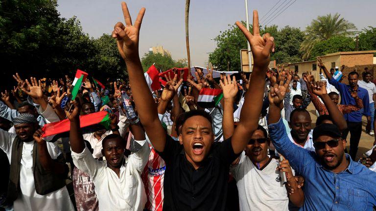 Des manifestants soudanais élèvent des signes de victoire alors que le président Omar al Bashir se retire