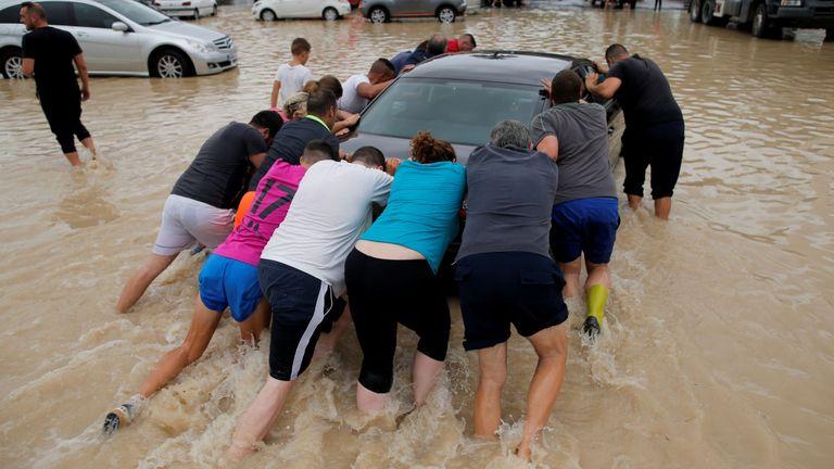 Des gens poussent une voiture dans un parking partiellement submergé alors que des pluies torrentielles s'abattent sur Orihuela, en Espagne.