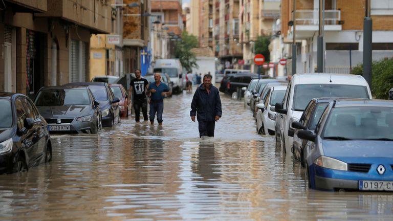 Les gens marchent dans une rue inondée alors que des pluies torrentielles s'abattent sur Orihuela