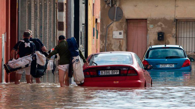 Les gens marchent dans une rue inondée à Almoradi