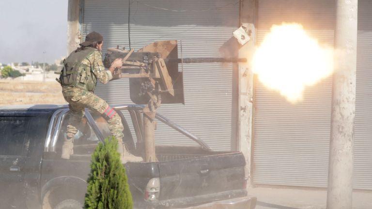 Un combattant rebelle syrien soutenu par la Turquie tire une arme dans la ville de Tal Abyad