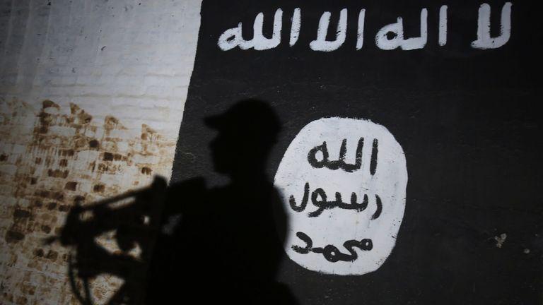 TOPSHOT - Un membre des forces irakiennes passe devant une peinture murale portant le logo du groupe État islamique (EI) dans un tunnel qui aurait été utilisé comme centre de formation par les djihadistes, le 1er mars 2017, dans le village d'Albu Sayf , dans la banlieue sud de Mossoul. Les forces irakiennes ont lancé le 19 février une importante campagne visant à reprendre le groupe djihadiste de l'État islamique à l'ouest de Mossoul, en reprenant l'aéroport puis en se dirigeant vers le nord. / AFP PHOTO / AHMAD AL-RUBAYE (Le crédit photo devrait correspondre à AHMAD AL-RUBAYE / AFP / Getty Images)
