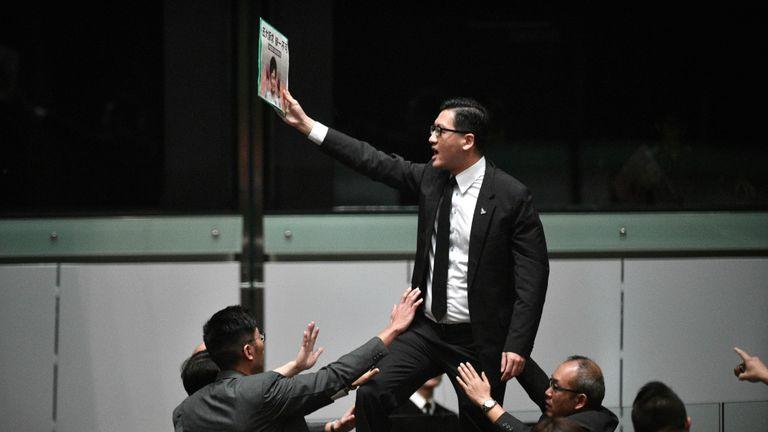 Le législateur pro-démocratie Lam Cheuk-ting (C) se lève et proteste peu avant que la directrice générale de Hong Kong, Carrie Lam (non représentée), quitte la salle pour la deuxième fois alors qu'elle tentait de présenter son discours politique annuel devant le Conseil législatif (Legco) de Hong Kong, le 16 octobre 2019. - La dirigeante assaillie de Hong Kong a abandonné le 16 octobre un discours sur l'état de l'Union, après qu'elle ait été chahutée par les législateurs de l'opposition lors de scènes chaotiques à l'intérieur de la législature de la ville. (Photo par Anthony WALLACE / AFP) (Photo par ANTHONY WALLACE / AFP via Getty Images)