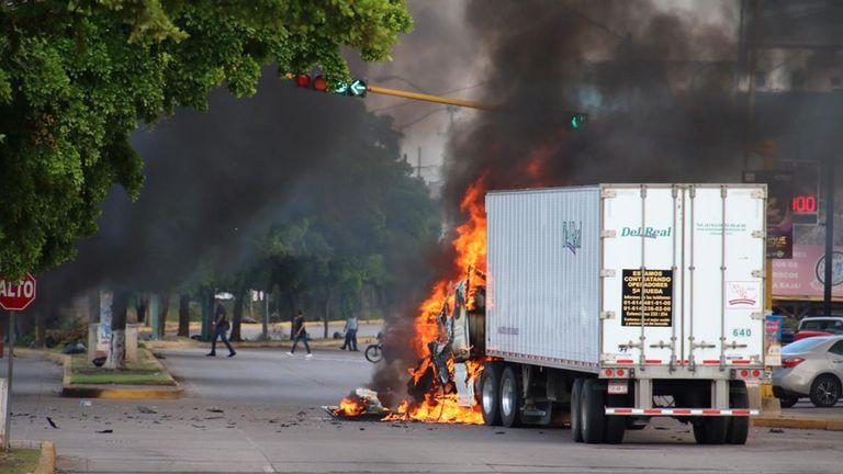 """Un camion brûle dans une rue de Culiacan, dans l'État de Sinaloa, au Mexique, le 17 octobre 2019. - Des hommes armés fortement armés dans des camions quatre par quatre ont mené jeudi une bataille intense contre les forces de sécurité mexicaines dans la ville de Culiacan, capitale de la prison. Le roi Joaquin """"El Chapo"""", l'état d'origine de Sinaloa chez Guzman. (Photo de STR / AFP) (Photo de STR / AFP via Getty Images)"""