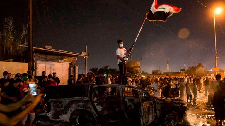 Un manifestant brandit un drapeau national alors qu'il se trouve sur un véhicule de police incendié à Basra