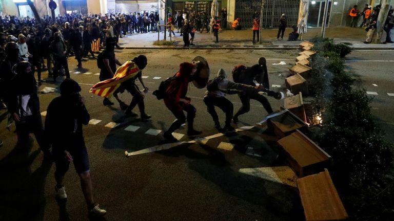 Les manifestants sont vus derrière une barricade lorsqu'ils se heurtent à la police