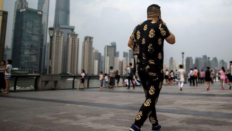 Cette photo prise le 15 juillet 2016 montre un homme portant une tenue avec des symboles du dollar en or alors qu'il marchait dans le Bund, surplombant le quartier financier de Pudong à Shanghai. La croissance du PIB de la Chine au deuxième trimestre est restée stable à 6,7%, a annoncé le gouvernement le 15 juillet, alors que la deuxième économie mondiale cherche la stabilité face à la noirceur croissante des perspectives mondiales.