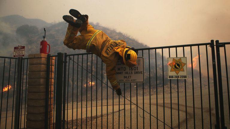 Un pompier saute par-dessus une porte verrouillée près du feu de Tick dans le sud de la Californie