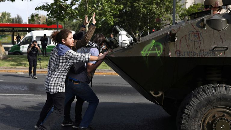 Des manifestants photographiés devant un véhicule de l'armée