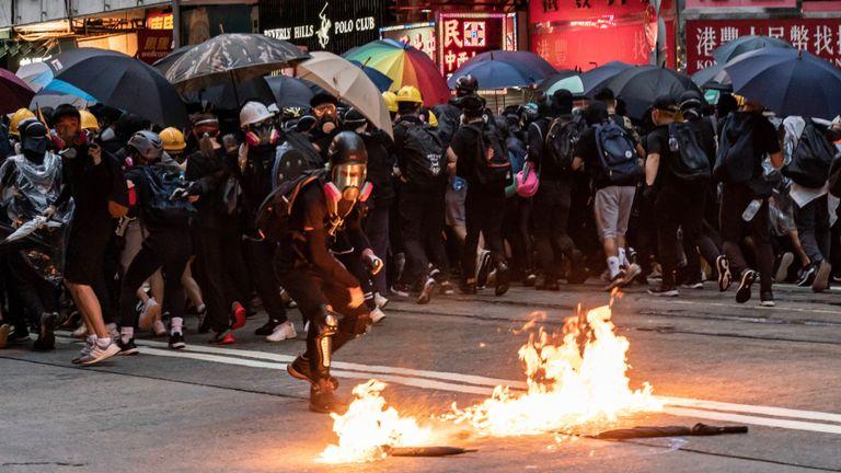Un manifestant masqué pro-démocratie lance un cocktail Molotov lors d'un affrontement avec la police