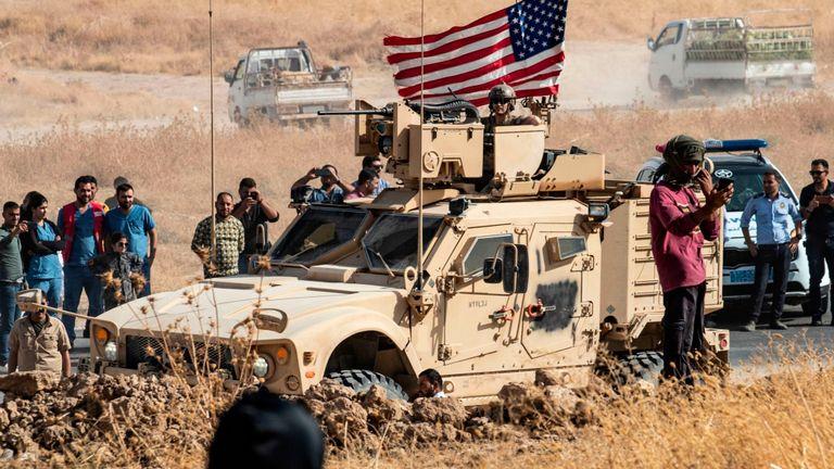 Des Kurdes syriens se rassemblent autour d'un véhicule blindé américain lors d'une manifestation contre les menaces turques de les attaquer