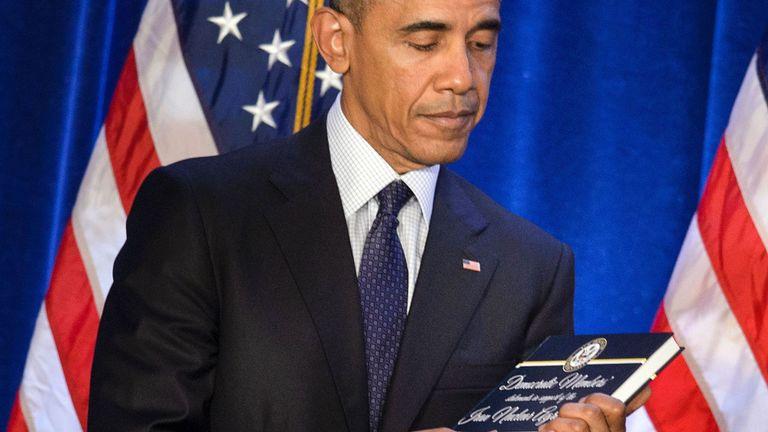 Le président des États-Unis, Barack Obama, détient une copie de l'accord sur le nucléaire iranien présenté par la chef de la minorité à la Chambre, Nancy Pelosi (D-CA), lors de la conférence sur les questions démocratiques à la Chambre, le 28 janvier 2016 à Baltimore, Maryland. / AFP / Brendan Smialowski (Le crédit photo doit se lire comme suit: BRENDAN SMIALOWSKI / AFP / Getty Images)
