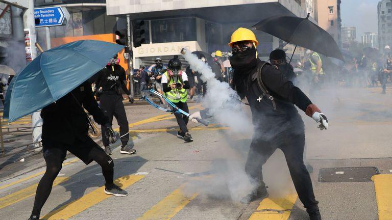 Un manifestant se prépare à frapper une cartouche de gaz lacrymogène avec une raquette de tennis à Hong Kong